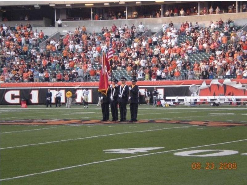 Honor Guard members presenting the colors in the middle of the football field