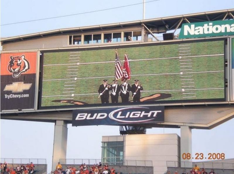 Large screen view of honor guard members on football field