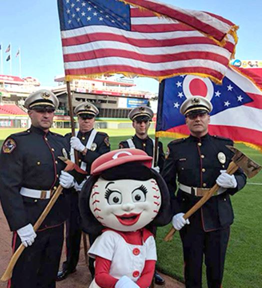 Firefighters posing for a photo with the baseball park mascot